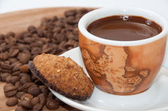 Integrated chocolate cookie and a cup of coffee with raw coffee Royalty Free Stock Images