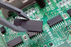 Integrated circuit. Holding an integrated circuit chip with printed circuit board as back ground Royalty Free Stock Photography