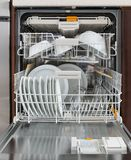 Integrated dishwasher with dishware in a kitchen. Home appliances. Closeup shot of an open integrated dishwasher full of dishware stock image