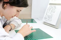Integrated microcircuit chip worker. Woman in white uniform checking or assembling components and chip on integrated microcircuit Stock Images