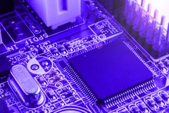 Integrated semiconductor microchip on blue circuit board representative of the high tech industry and computer science Royalty Free Stock Photography