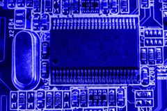 Integrated semiconductor microchip on blue circuit board representative of the high tech industry and computer science Royalty Free Stock Photo