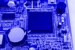 Integrated semiconductor microchip on blue circuit board representative of the high tech industry and computer science Stock Photos