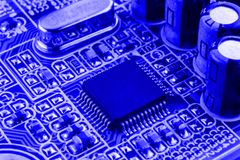 Integrated semiconductor microchip on blue circuit board representative of the high tech industry and computer science Stock Photography