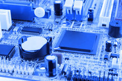 Integrated semiconductor microchip microprocessor on blue circuit board representative of the high tech industry and computer scie. Nce toned Stock Photo