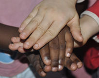 INTEGRATION CONCEPT. Hands of girls of different colors on each other as aimed at fostering coexistence with foreign populations as a concept of integration Royalty Free Stock Images