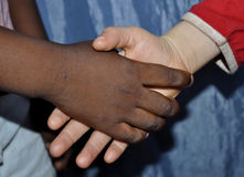 INTEGRATION CONCEPT. Hands of girls of different colors on each other as aimed at fostering coexistence with foreign populations as a concept of integration Stock Images
