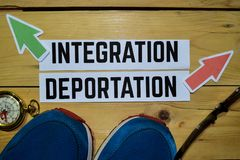 Integration or Deportation opposite direction signs with sneakers, eyeglasses and compass on wooden stock photo