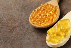 Integratore alimentare delle capsule dell'olio di pesce in un cucchiaio di legno Fotografie Stock Libere da Diritti