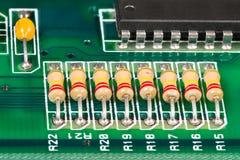 Integrerat - strömkrets, motstånd och kondensator som lödas på PCB arkivfoto