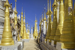 Intein temple stupas. Avenue through crowd of tall golden mini stupas in Burmese temple grounds royalty free stock images