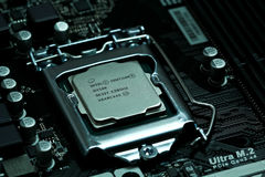 Intel CPU installed on a motherboard. A photograph of an intel g4560 kaby lake 7th generation cpu processor component installed and braced on a motherboard. The stock photos