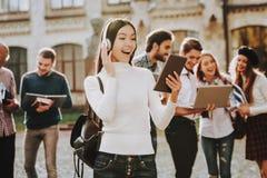 Inteligência headphones Menina feliz campus imagens de stock royalty free