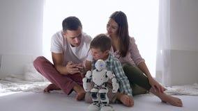 Inteligencia artificial, juegos felices de la familia con el robot en teledirigido del teléfono móvil que se sienta en piso