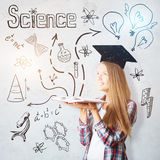 Intellect concept. Attractive cheerful young caucasian woman with open book, drawn mortarboard and other education related drawings. Intellect concept stock photos