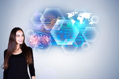 Intellect and future concept. Portrait of smiling young european woman standing on grey background with abstract brain interface. Intellect and future concept stock photography