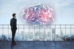 Intellect and research concept. Back view of young businessman on rooftop looking at abstract glowing polygonal brain on city background. Intellect and research stock images