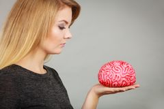 Woman thinking and holding fake brain Royalty Free Stock Photos
