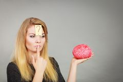 Woman thinking and holding fake brain Royalty Free Stock Images