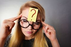 Woman having question mark on forehead thinking Royalty Free Stock Image