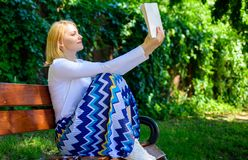 Intellectual hobby. Lady pretty bookworm busy read book outdoors sunny day. Girl sit bench relaxing with book, green. Nature background. Woman concentrated royalty free stock photos