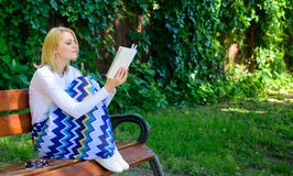 Intellectual hobby. Lady pretty bookworm busy read book outdoors sunny day. Woman concentrated reading book in garden. Girl sit bench relaxing with book, green stock image