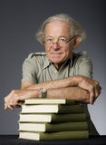 Intellectual Mature Man. Waist-up view of mature intellectual man with stack of books. Studio photo Stock Image