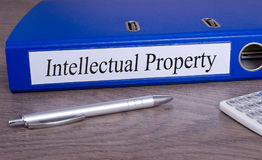 Intellectual Property - blue binder in the office. Intellectual Property - blue binder with text on desk in the office stock images