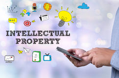 INTELLECTUAL PROPERTY. Person holding a smartphone on blurred cityscape background Royalty Free Stock Image