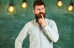 Intellectual task concept. Bearded hipster in shirt, chalkboard on background. Guy thinking with thoughtful expression. Man with beard and mustache on Stock Photos