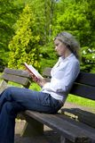 Intellectual woman. Woman reading on bench outdoor in park Royalty Free Stock Photos