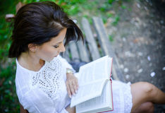 Intellectual woman reading a book in the park Stock Image