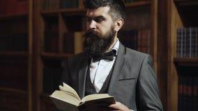 Intellectueel eliteconcept Ouderwetse mens die een boek lezen bij boekenkast in bibliotheek Aristocraat op bezig gezicht met boek stock videobeelden