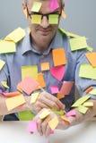 Intellectuel occupé couvert de notes de bâton Photographie stock libre de droits