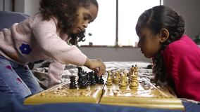 Two smart little girls playing chess on bed stock video footage