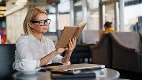 Intelligent affärskvinna som tycker om bokläsning i kafé under kaffeavbrott stock video