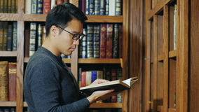Intelligent Asian man looking a book in the library. Intelligent yong Asian man looking a book in the library stock footage