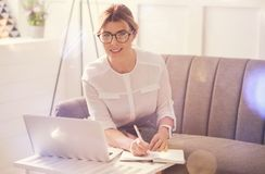 Intelligent attractive businesswoman looking at you. Interesting job. Intelligent attractive delighted businesswoman sitting in front of the laptop and looking Stock Photos