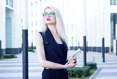 Intelligent blond with red lips and notebook looks into the distance on the background of the business center Royalty Free Stock Photo