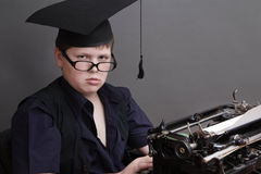 Intelligent boy with glasses and typewriter Royalty Free Stock Photography