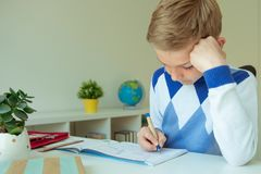 Intelligent boy makes homework in his room. Intelligent boy makes homework at desk in his room royalty free stock image