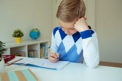 Intelligent boy makes homework in his room. Intelligent boy makes homework at desk in his room stock photos