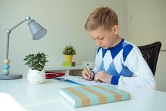 Intelligent boy makes homework in his room. Intelligent boy makes homework at desk in his room stock photography