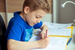 Intelligent boy makes homework in his room. Intelligent boy makes homework at desk in his room royalty free stock photography