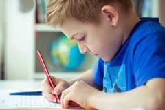 Intelligent boy makes homework in his room. Intelligent boy makes homework at desk in his room royalty free stock images
