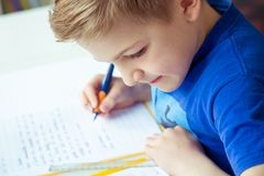 Intelligent boy makes homework in his room. Intelligent boy makes homework at desk in his room stock images