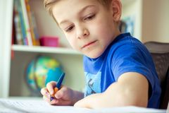 Intelligent boy makes homework in his room Royalty Free Stock Images