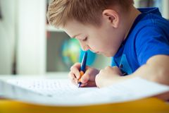 Intelligent boy makes homework in his room. Intelligent boy makes homework at desk in his room stock image