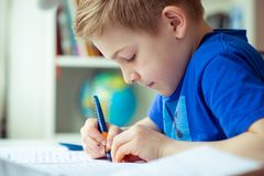 Intelligent boy makes homework in his room. Intelligent boy makes homework at desk in his room royalty free stock photos