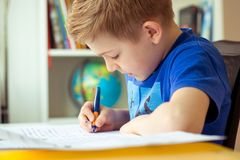 Intelligent boy makes homework in his room. Intelligent boy makes homework at desk in his room royalty free stock photo